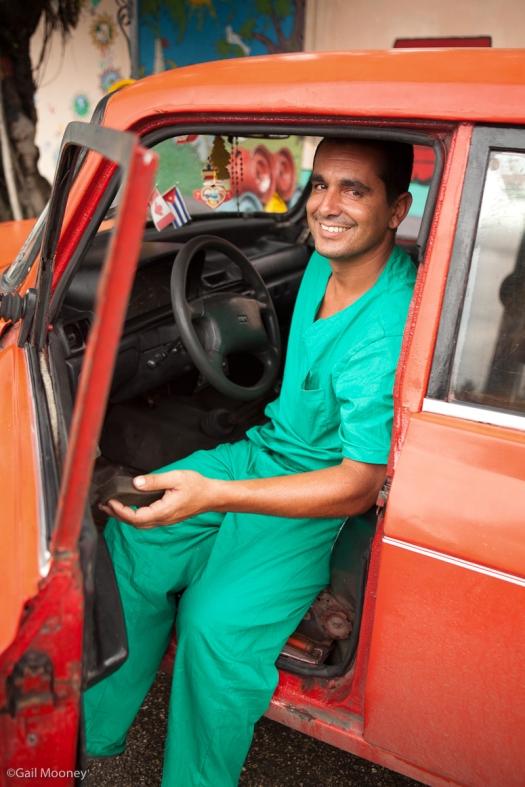 Man with armarall, cleaning car. Havana, Cuba